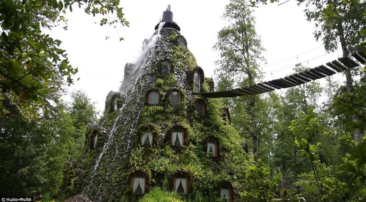 Chilean lodge covered in a living wall, complete with waterfall cascading over building